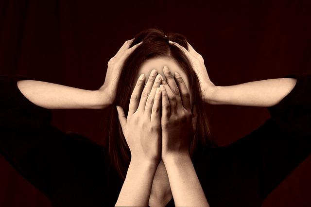 Kobieta zakrywa twarz rękami