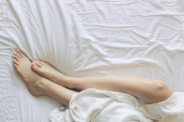 Nogi leżące na łóżku